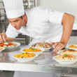 Stock Photo: Chef Garnishing Dishes At Counter
