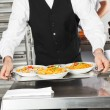 Stock Photo: Waiter Holding Pasta Dishes In Tray