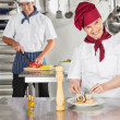 Stockfoto: Female Chef Garnishing Dish In Kitchen