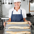 Female Chef Presenting Loafs In Kitchen — Stock Photo #21415465