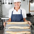 Female Chef Presenting Loafs In Kitchen — Stock Photo