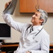 Radiologist Reviewing X-ray At Clinic - Stock Photo