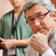 Male Doctor With Hand On Chin - Stock Photo