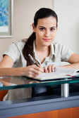 Female Receptionist Writing In Book — Stock Photo