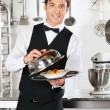 Waiter Lifting The Cover Of Cloche - Foto Stock