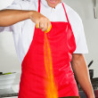 Chef Adding Turmeric Powder In Pan - Stock Photo