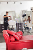 Hairdresser Styling Customer's Hair At Parlor — Stock Photo