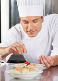 Chef Sprinkling Spices On Dish — Stock Photo