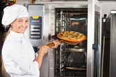 Beautiful Chef Placing Pizza In Oven — Stock Photo