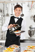 Waiter Lifting The Cover Of Cloche — Stock Photo