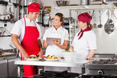 Chefs Using Tablet Computer At Kitchen Counter — Stock Photo
