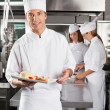 Stock Photo: Chef Presenting Dish In Commercial Kitchen
