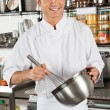 Male Chef Whisking Egg In Kitchen — Stock Photo #21533461