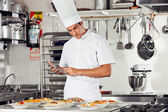 Male Chef Using Digital Tablet In Kitchen — Stock Photo