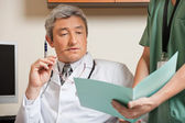 Doctor Reading Patient's File — Stock Photo