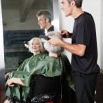 Hair Stylist Straightening Customer's Hair — Stock Photo