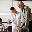 Man Being Assisted By Nurse To Walk Zimmer Frame - Stock Photo