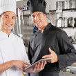 Foto Stock: Happy Chefs Holding Digital Tablet
