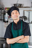 Male Chef With Arms Crossed In Kitchen — Stock Photo