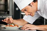шеф-повар мужчины гарнировать блюдо — Стоковое фото