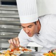 Male Chef Garnishing Pasta Dishes - Stock Photo