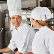 Male Chef With Colleague At Kitchen — Stock Photo