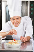Happy Male Chef Sprinkling Spices On Dish — Stock Photo