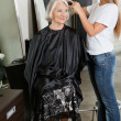Stock Photo: Hairdresser Straightening Woman's Hair At Parlor