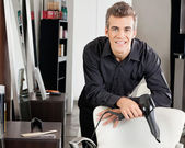 Hairstylist With Blower Leaning On Chair — Stock Photo