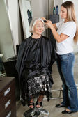 Hairdresser Straightening Woman's Hair At Parlor — Stock Photo