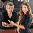 Stock Photo: Hairdresser With Woman Paying Through Cellphone At Counter