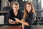 Hairdresser With Woman Paying Through Cellphone At Counter — Stock Photo