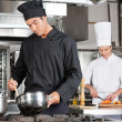 Stock Photo: Chef Cooking Food With Colleague Chopping Vegetable