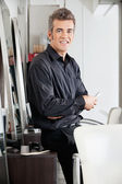 Male Hairstylist With Scissors Leaning On Cabinet — Stock Photo