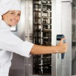 Female Chef Opening Oven Door — Stock Photo