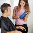 Hairdresser Presenting Shampoo Bottle To The Client - Stock Photo
