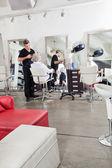 Hairstylist Ironing Customer's Hair — Zdjęcie stockowe