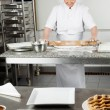 Chef Rolling Dough With Sweet Food In Foreground — Stock Photo