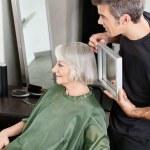 Hairdresser Holding Mirror Behind Senior Woman — Stock Photo #21988211