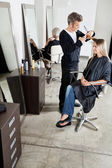 Hairdresser Cutting Client's Hair In Parlor — Stock Photo