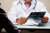 Radiolog vid skrivbord håller röntgen — Stockfoto
