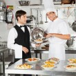 Chef Giving Pasta Dish To Waiter - Stock Photo