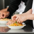 Chefs Garnishing Pasta Dishes - Stock Photo