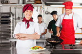 Female Chef With Arms Crossed In Kitchen — Stock Photo