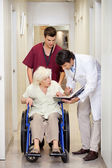 Medical Professionals With Patient In Corridor — Stock Photo