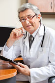 Doctor Sitting At Desk In Clinic — Foto de Stock