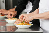 Chefs Garnishing Pasta Dishes — Stock Photo