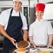 Happy Chefs With Variety Of Sweet Dishes — Stock Photo #22220237