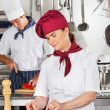 Female Chef Garnishing Dish In Kitchen — Foto de Stock