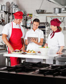 Chefs Using Digital Tablet In Kitchen — Stock Photo